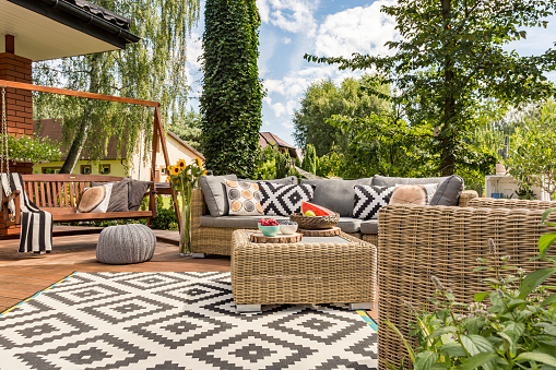 Outdoor patio furniture and carpet in a green backyard