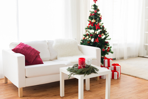 White couch with red pillows beside a white table and a decorated christmas tree in red
