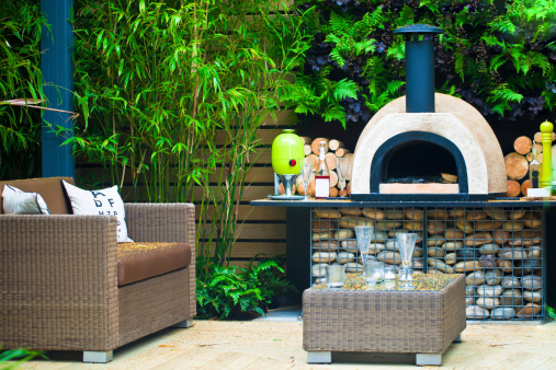 Outdoor firepit in a green garden with outdoor patio furniture