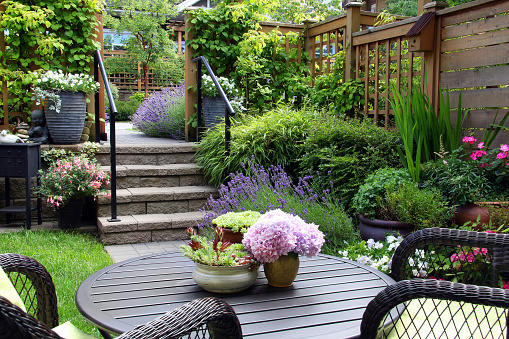 Black patio furniture in a green backyard with a wooden deck