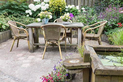 wooden chairs and table in a luscious green backyard